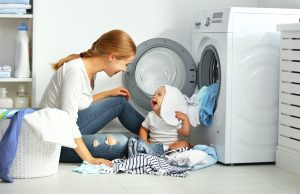 Mom doing laundry with baby